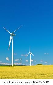 three wind turbines and blue sky