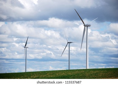 Three wind turbines on a blue and cloudy sky. Sustainable energy.