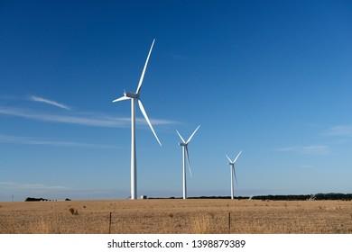 Three wind turbines on a farm in an Australian landscape.