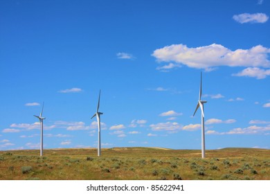 Three wind turbines on the prairie with blue sky