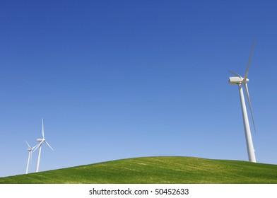 three windmills in an idyllic green meadows and blue sky