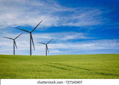 Three windmills on a green meadow under dramatic sky