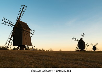 Three windmills on a small hilltop on a spring evening during sunset. Location Resmo on Oland, Sweden.