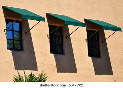 Three windows with awnings against terra cotta colored wall