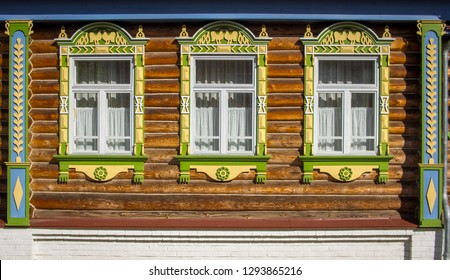 Three windows with carved platbands on the decorated facade of the wooden house. Three objects in line. Colorful photoghraphy. Yaroslavl region, Russia.