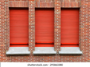 three windows with red roller shutter