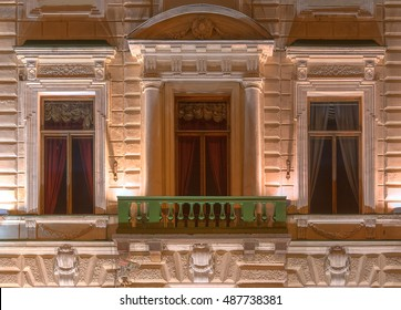 Three windows in a row and balcony on night illuminated facade of urban office building front view, St. Petersburg, Russia