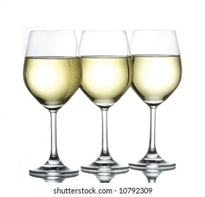 three wine glasses filled with white wine side by side