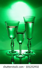 Three wineglasses on the mirror in the green light
