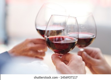 Three wineglasses with red cabernet held by group of toasting friends