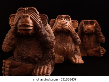 Three wise monkeys. Figurines of wood on a black background.