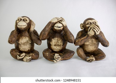 Three Wise Monkeys in a row, Hear no evil, See no evil, Speak no evil, brown monkeys on a white background.