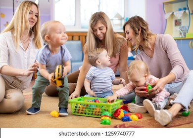 Three woman friends with kids toddlers having a fun sitting on the floor in playroom