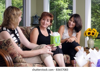 Three Woman Giving A Surprise Gift To Their Friend