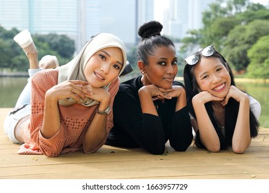 Three woman Malay Chinese Indian Asian Malaysian outdoor green park lake nature lying on front wooden deck hand on cheek talk smile chat emotion expression
