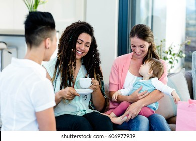 Three woman smiling and sitting on sofa with a baby