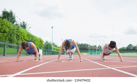 Three woman stretching on running track in stadium