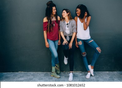 Three woman wearing fashionable clothes standing against a wall outdoors. Happy looking women standing against a wall looking at each other.