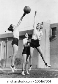 Three women with basketball in the air