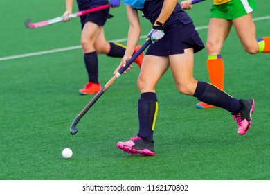 three women battle for control of ball during field hockey game