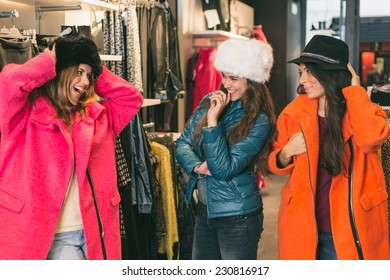 Three Women in a Clothing Store with Colorful Coats. The women are Playing with Strange Clothes and they look each other smiling