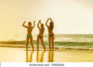 Three women dancing on the beach and enjoying sunset and sea. Back view. Tropical vacation and holiday on the beach concept.