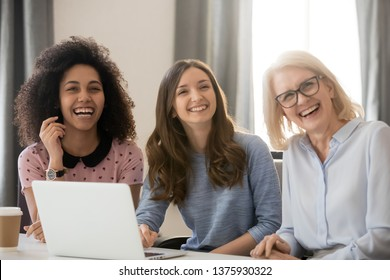 Three women different ethnicity and ages looking away laughing sitting at workplace gather at corporate meeting take break telling joke stories anecdotes, friendly collective and fun at work concept