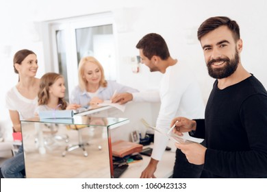 Three women of different generations at reception in beauty salon with hairdressers. Women fill out documents at reception desk at beauty salon.