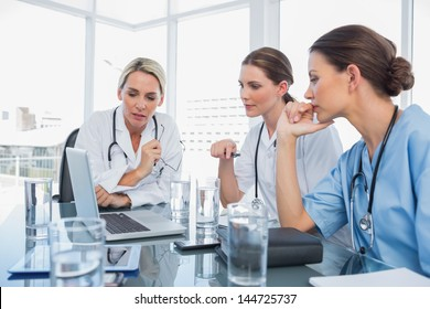 Three women doctors watching a laptop during a meeting