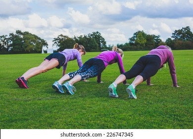 Three women are doing push ups on the grass in the park