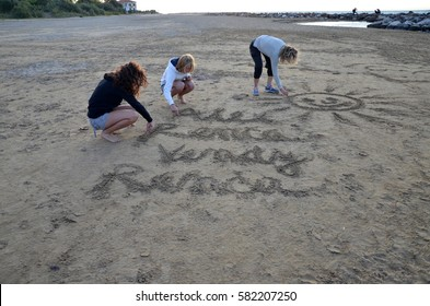 three women drawing into a sand on the beach