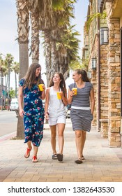 Three women drinking fruit smoothies while walking and talking outdoors down a commercial street with retail shops. Women living a healthy lifestyle
