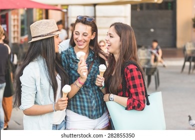 Three  women eating ice cream in the city, talking each other and smiling. This is a mixed race group, one girl is half asian and one is middle eastern. Lifestyle, friendship and urban life concepts.