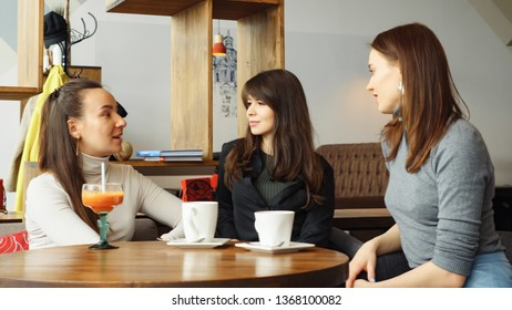 Three women girlfriends in a cafe are talking and drinking their beverages. Friendly meeting in the cafe in weekend. Front view.