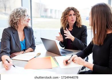 drei Frauen, die in einem modernen Gebäude geschäftlich zusammenkommen
