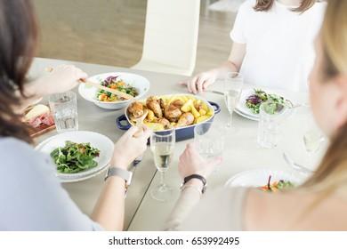 Three women having dinner together. Friends enjoying dinner with chicken, potato, salad and wine