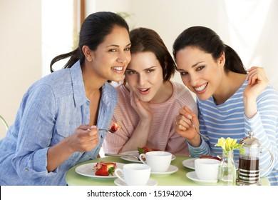 Three Women Having Snack In Cafe