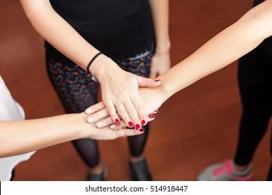 three women holding hands in gym