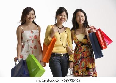 Three women holding shopping bags.