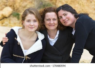 three women hugging on a beach