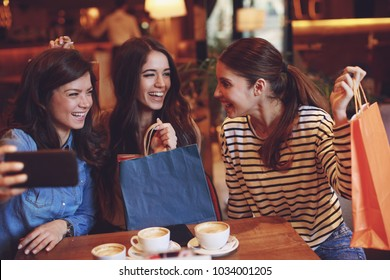 Three women making selfie after shopping in a cafe