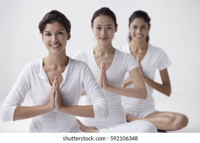 three women of mixed race sitting with legs crossed, arms in namaste, smiling at camera