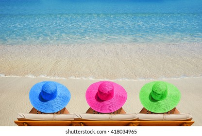Three women on beach in bright hats traveling