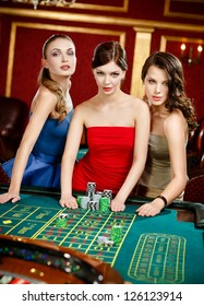 Three women place a bet playing roulette at the gambling house