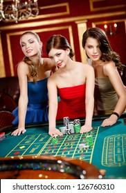 Three women place a bet playing roulette at the casino club