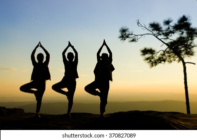 three women practicing Yoga in the mountain at before sunset