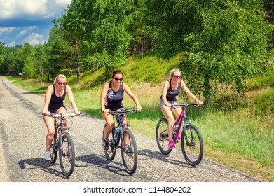 three women ride bicycles