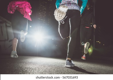 Three women running in the night in the city center