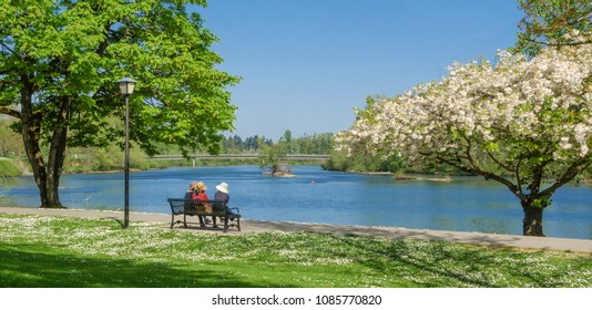 Three women sit on a bench enjoying a springtime view of the Willamette River along the bike path.