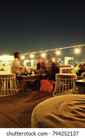 Three women sitting on a chic rooftop bar at night in Manhattan. Stools and table, large string lights along the balcony, lights of New York City in the background. Low light photography, motion blur.
